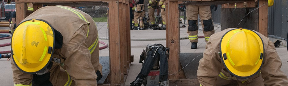 firefighters crawling on their knees during training